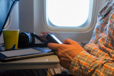 Hand of man browsing gadget in aircraft