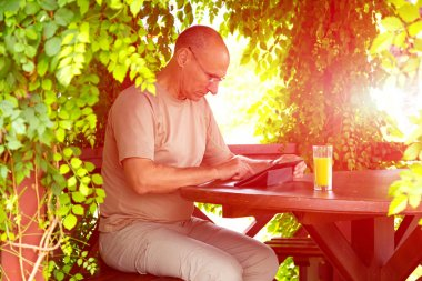 Casual dressed man with gadget and glass of orange juice sitting in wood arbor