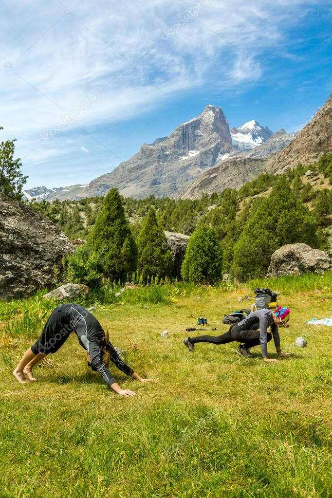 Young women doing morning fitness in mountain landscape