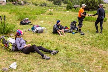Hikers break on grassy lawn