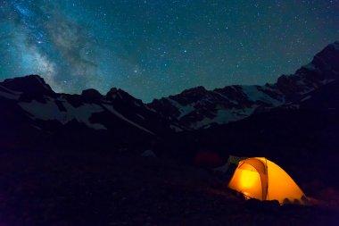 Night mountain landscape with illuminated tent