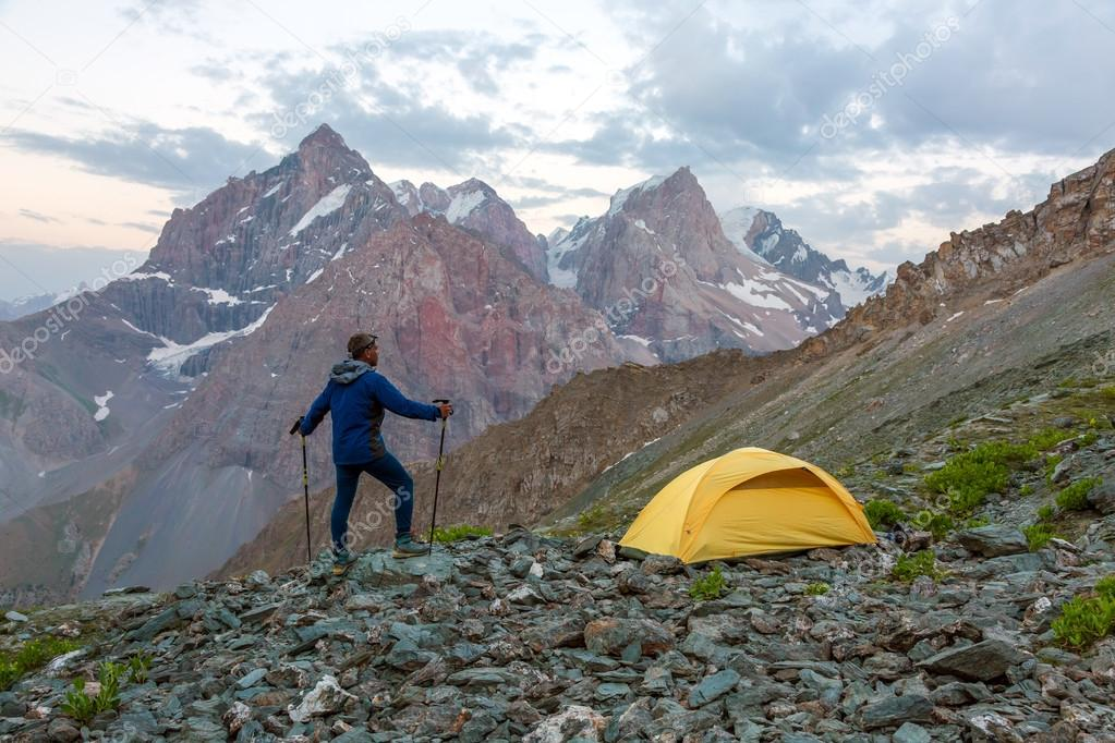 Hiker camping tent and mountain landscape