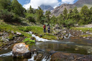 Hikers staying on shore of mountain rive