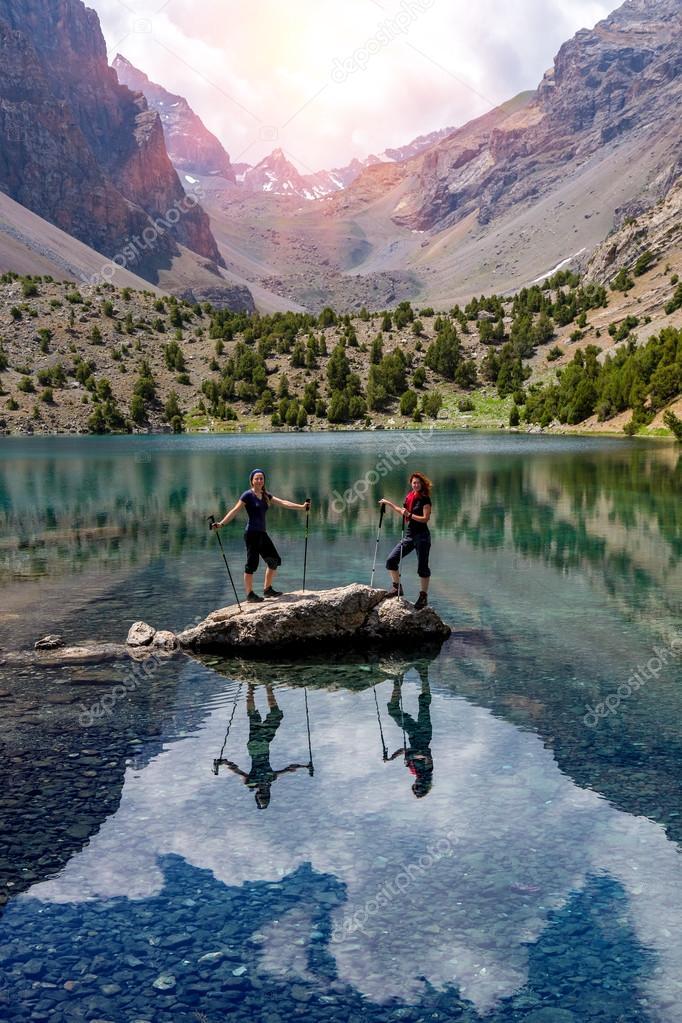 Two smiling females staying Among Blue Mountain Lake