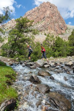 Two hikers crossing fast flowing river