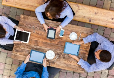 Business people with Digital Devices at cafe Table