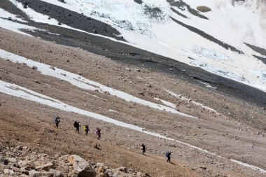 Group of Hikers Walking on Deserted Rocky Terrain