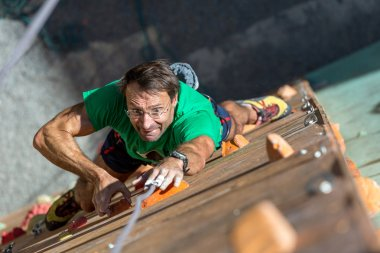 Portrait of Mature Athlete on Extreme Climbing Wall