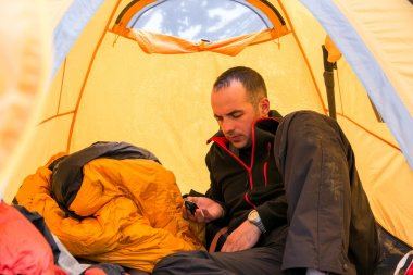 Climber inside Camping Tent Using Gadget