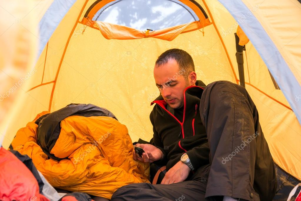 Climber inside Camping Tent Using Gadget
