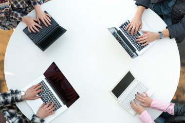 Top View of Rounded Desk with Four Laptops and People Hands Typing on Keyboard