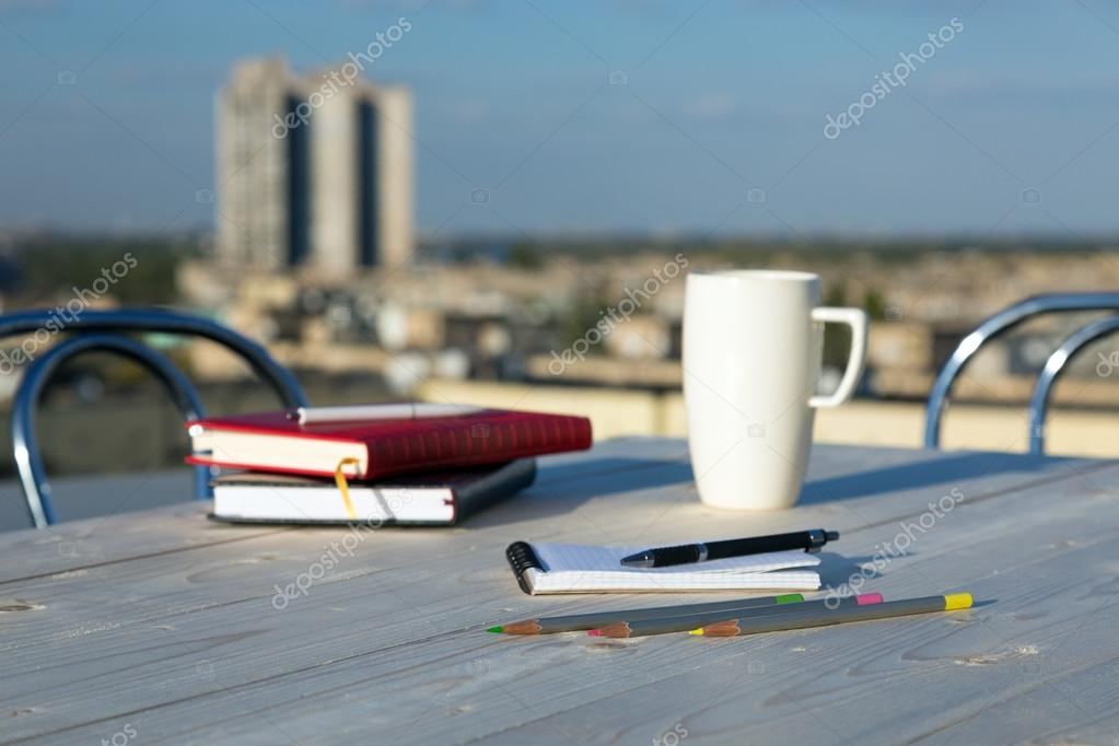 Business and Lifestyle Items on Wooden Table at Roof Top Cafe Terrace with Urban Landscape Outdoor Background Color Pencils Coffee Mug Notepads