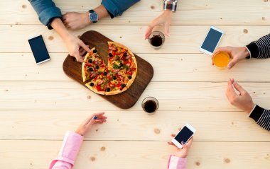 Hands of People at Wood Cafe Pizza Table with Drinks Food and Electronic Gadgets