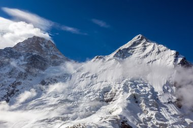 Majestic View of High Altitude Snowbound Mountain Peaks with Glaciers Rocks Snow Clouds and Blue Sky