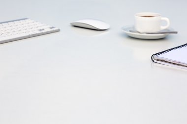 Soft Blurred Office Background with Computer Keyboard Mouse Coffee Mug and Notepad Side View Focus on Notepad
