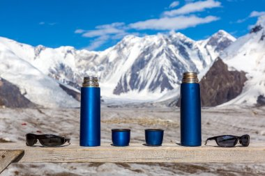 Two Blue Travel Thermoses Cups and Sunglasses on Wood Table and Mountain Landscape