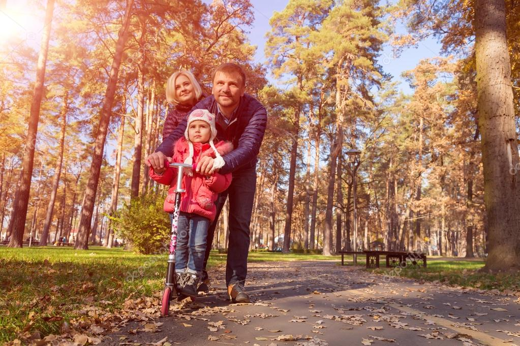 Happy Family with Little Daughter on Walk in Park