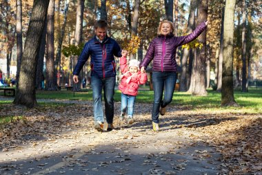 Young Family in Autumnal Forest Running