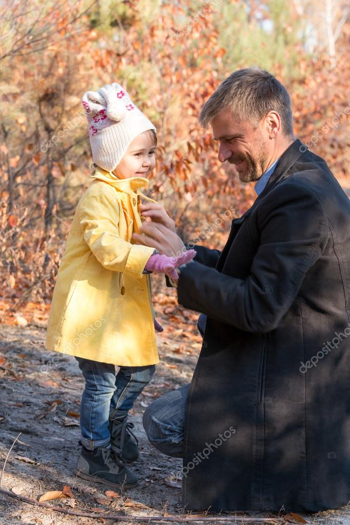 Father Helping Little Baby Daughter to Wear Coat