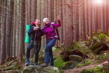 Man and Woman Hikers Staying in Dense Old Forest Smiling and Pointing