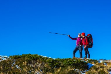 Simple Outdoor Sport concept Image Two Hikers pointing Gesture large space blue Sky