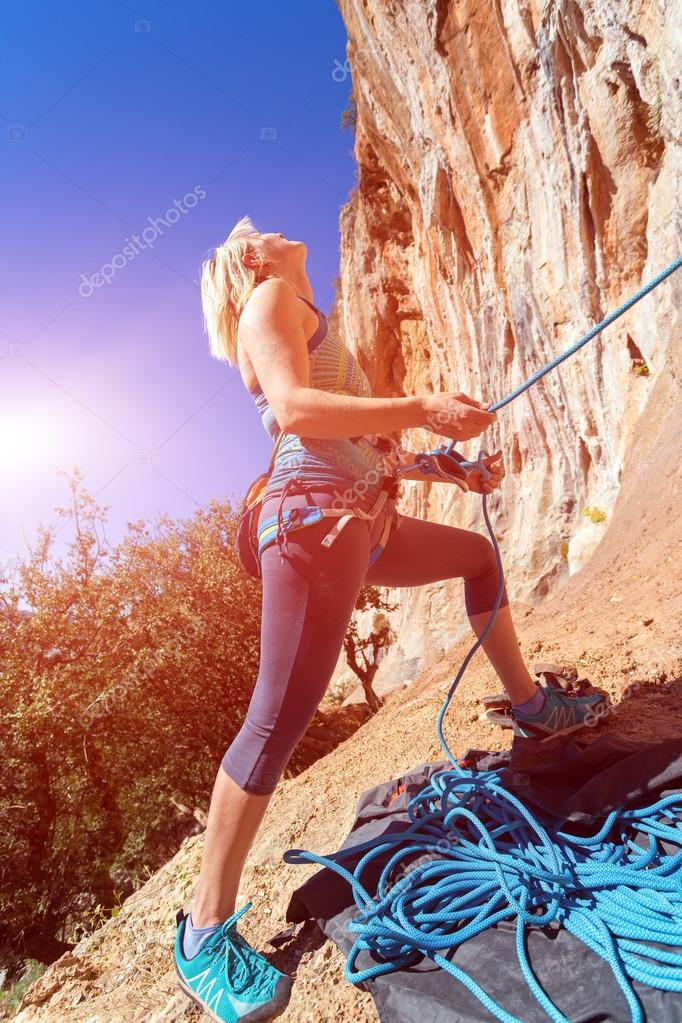 Blond Female Athlete belaying her Climbing Partner with Rope