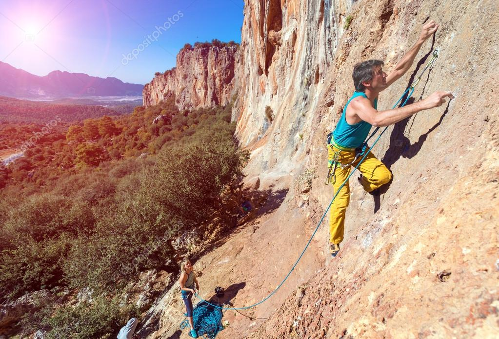 Team of Climbers Man and Woman ascending orange bright rocky Wall with rope and gear