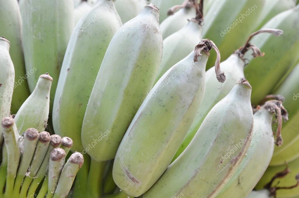 bunch of raw banana on bamboo table