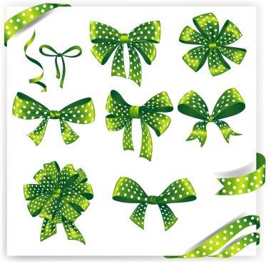 Set of green polka dot gift bows with ribbons.