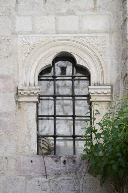 antique window with decorations on the white stone wall