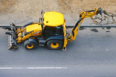 Excavator JCB 3cx jackhammer smash old asphalt on city road - Moscow, Russia, may 18, 2020