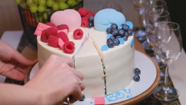 Eine schwangere Frau bringt ein Stück Kuchen zu einer Geschlechterparty, mit zitternder Hand, Lebensstil. Das Geschlecht des ungeborenen Kindes feiern - es oder sie