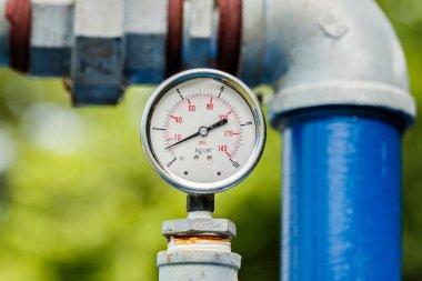 Water pressure meter installed on a blue pipe