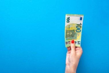Elinde para, elinde banknot olan bir poster. Mavi arka planda 100 avroluk banknot var. Finansal temalar için mavi arkaplan