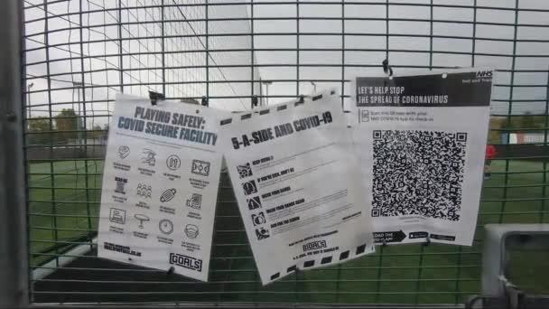 Covid bezpečné značky spolu s kontaktní stopa a stopa aplikace visí na plot na cíle Ruislip