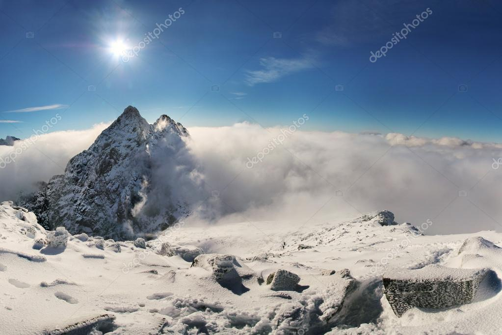 Mountain peak covered in clouds in sunny day