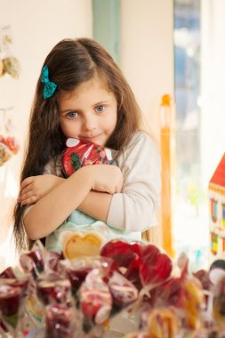 Greed  little girl with lollipop in candy store