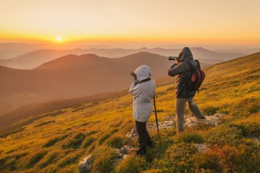 Photographers takes a sunset in the mountains