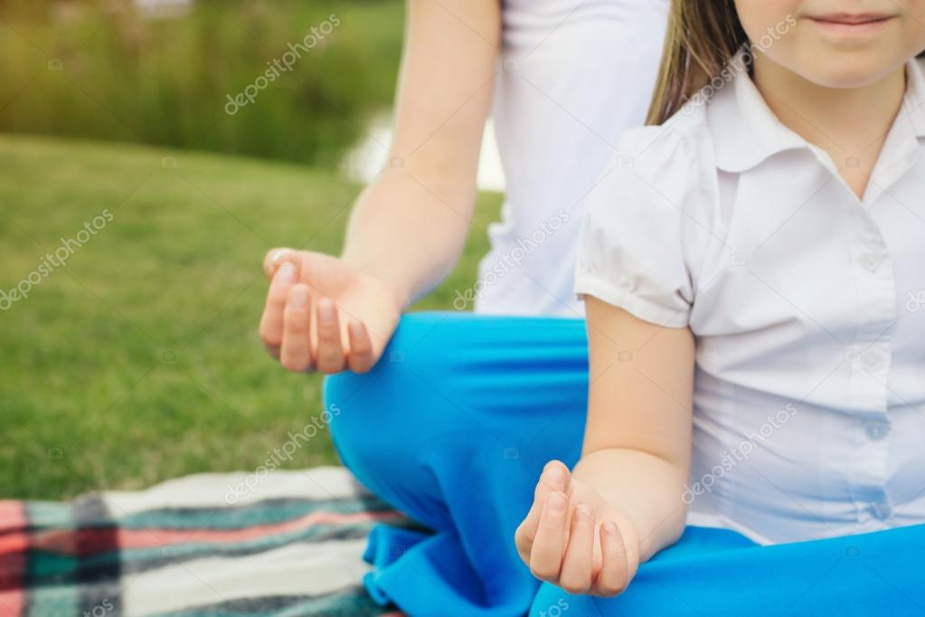 Mother with daughter doing yoga exercise