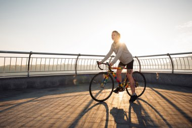 Young woman cycling in the morning city
