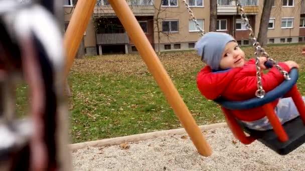 Roztomilý chlapeček v červeném saku a modrý klobouk na řetízku v parku. Zimní čas 4K zpomalení