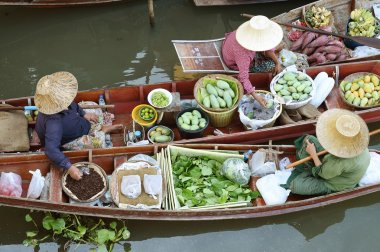 Wooden boats are loaded with fruits from the orchards at Tha kha floating market .