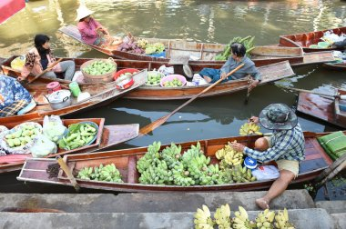 Wooden boats are loaded with fruits from the orchards at Tha kha floating market
