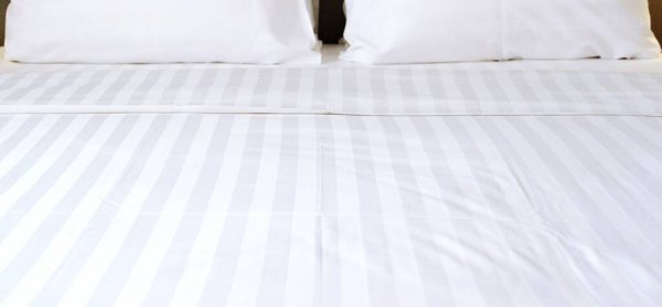 Comfortable white bed set looked soft and clean. Focus on white bed sheet