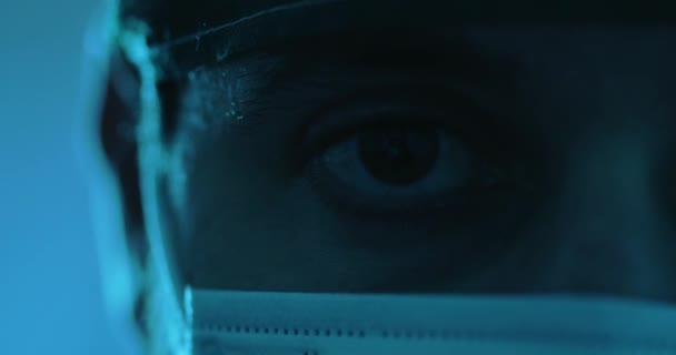 cropped footage of man, eye and medical mask on face