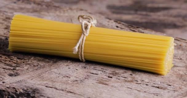 yellow long spaghetti on wooden table. Raw spaghetti.