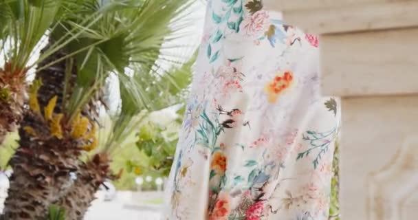 Mladá žena v dlouhých letních šatech s květinami ornament procházky v letním parku