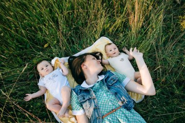 Portrait Of Happy young Family spending time outdoor on a summer day. Mother and Funny twins sisters newborn babies lying on grass