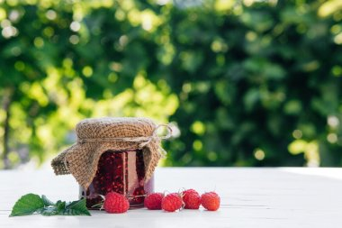 Home- made Raspberry jam in a jar on the wooden table in the garden