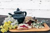Malinový džem a chleba s máslem v jar a horký bylinkový čaj na dřevěný stůl oběd snídaně